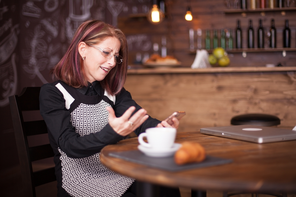 Adult businesswoman amazed while using her phone