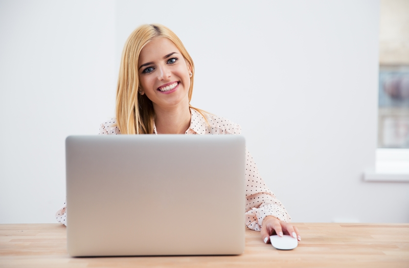woman smiling in front of the laptop