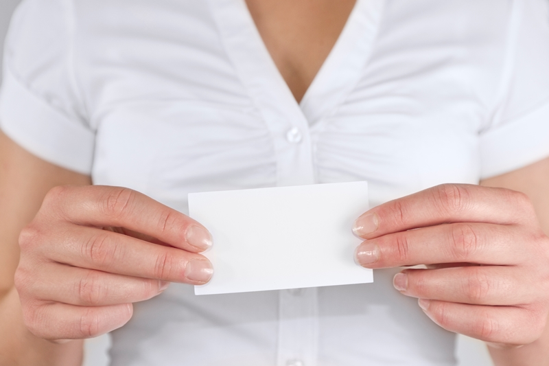 Woman holds out business card