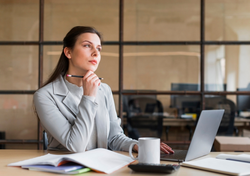 Woman thinking infront of the laptop